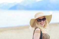Όμορφο ξανθό πορτρέτο στην παραλία με το καπέλο και τα γυαλιά ηλίου Στοκ Εικόνα