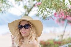Όμορφο ξανθό πορτρέτο στην παραλία με το καπέλο και τα γυαλιά ηλίου Στοκ φωτογραφία με δικαίωμα ελεύθερης χρήσης
