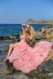 Όμορφο ξανθό προκλητικό φόρεμα γυναικών που στέκεται στους βράχους σε Santorini Στοκ Εικόνα