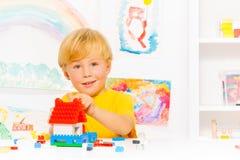 Όμορφο ξανθό σπίτι οικοδόμησης αγοριών Στοκ Φωτογραφίες