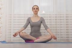 Όμορφο ξανθό τέντωμα γιόγκας άσκησης γυναικών στο σπίτι στο μπλε χαλί στο γκρίζο κομπινεζόν και τις ρόδινες κάλτσες Στοκ Φωτογραφία