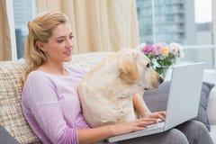 Όμορφο ξανθό χρησιμοποιώντας lap-top στον καναπέ με το σκυλί κατοικίδιων ζώων Στοκ Φωτογραφίες