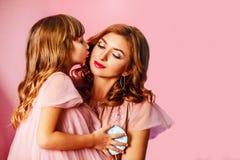 Όμορφο ξανθό mom με τη χαριτωμένη κόρη στο ρόδινο υπόβαθρο στο στούντιο Η ημέρα της ευτυχούς μητέρας, κόρη αγκαλιάζει mom και φιλ στοκ εικόνα