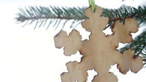Όμορφο ξύλινο παιχνίδι υπό μορφή snowflakes που κρεμούν στο χριστουγεννιάτικο δέντρο το χειμώνα απόθεμα βίντεο