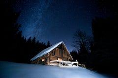 Όμορφο ξύλινο σπίτι στο χειμερινό δάσος κάτω από τα αστέρια Στοκ Εικόνα