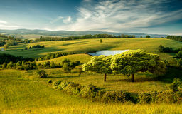 Όμορφο λοφώδες τοπίο με τη λίμνη και τον μπλε νεφελώδη ουρανό στοκ φωτογραφία
