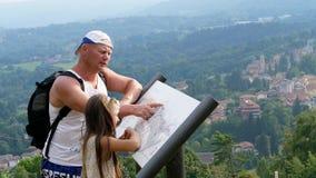 Όμορφο πάρκο στα αλπικά βουνά άτομο και ένα κορίτσι, παιδί, τουρίστες, χάρτης μελέτης του πάρκου, ενάντια στο σκηνικό γραφικού απόθεμα βίντεο