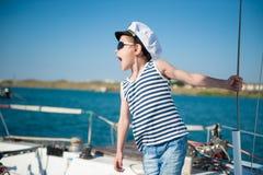Όμορφο παιδάκι που φορούν το πουκάμισο ναυτικών και το καπέλο καπετάνιου και γυαλιά ηλίου που δίνουν τις διαταγές Στοκ φωτογραφίες με δικαίωμα ελεύθερης χρήσης