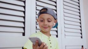 Όμορφο παιδάκι στην μπλούζα και την ΚΑΠ που ακούει τη μουσική στα ακουστικά από το γκρίζο smartphone και το χορό φιλμ μικρού μήκους