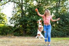 Όμορφο παιχνίδι κοριτσιών με ένα κουτάβι λαγωνικών Στοκ φωτογραφία με δικαίωμα ελεύθερης χρήσης