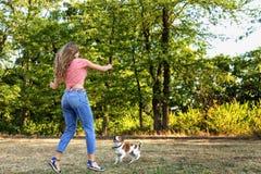 Όμορφο παιχνίδι κοριτσιών με ένα κουτάβι λαγωνικών Στοκ εικόνα με δικαίωμα ελεύθερης χρήσης