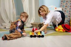 Όμορφο παιχνίδι μητέρων και αγοριών παιδιών μαζί εσωτερικό Στοκ φωτογραφία με δικαίωμα ελεύθερης χρήσης