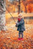 Όμορφο παιχνίδι μικρών κοριτσιών που αλιεύει με ένα παιχνίδι κλάδων και ψαριών Στοκ Εικόνα