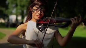 Όμορφο παιχνίδι νέων κοριτσιών στο ηλεκτρικό βιολί στο όμορφο πάρκο φιλμ μικρού μήκους