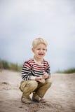 Όμορφο παιχνίδι αγοριών με την άμμο στην παραλία Στοκ Φωτογραφίες