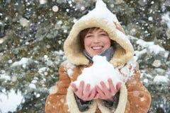 Όμορφο παιχνίδι γυναικών με το χιόνι δέντρα χειμερινού στα υπαίθρια, χιονώδη έλατου στο δάσος, που φορά ένα sheepskin παλτό Στοκ Φωτογραφία