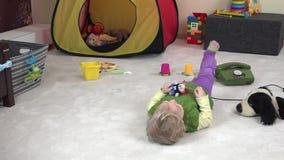 Όμορφο παιχνίδι κοριτσάκι μεταξύ των παιχνιδιών στο δωμάτιό της Χρόνος διασκέδασης στην παιδική ηλικία φιλμ μικρού μήκους