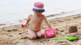 Όμορφο παιχνίδι μικρών κοριτσιών με το φτυάρι και άμμος στην παραλία κοντά στον ποταμό φιλμ μικρού μήκους