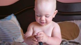Όμορφο παιχνίδι μωρών με τη χτένα στο κρεβάτι Χαμογελά και προσπαθεί να κτενιστεί Παιδί 1 έτος Στη χτένα είναι ένας καθρέφτης απόθεμα βίντεο