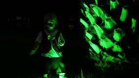 Όμορφο παιχνίδι μωρών με τους πράσινους φοίνικες backlight τη νύχτα Η ασυνήθιστη σκιαγραφία ενός μωρού απόθεμα βίντεο