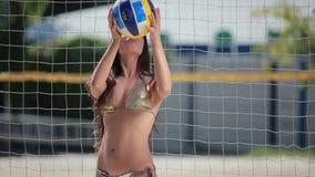 Όμορφο παιχνίδι brunette με τη σφαίρα πετοσφαίρισης ` s κοντά στο δίχτυ σε μια παραλία απόθεμα βίντεο