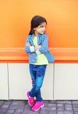 Όμορφο παιδί μικρών κοριτσιών που φορά ένα ελεγμένο πουκάμισο που κοιτάζει στο σχεδιάγραμμα πέρα από ζωηρόχρωμο στοκ εικόνα