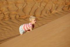 Παιδί που αναρριχείται στον αμμόλοφο άμμου Στοκ Εικόνες