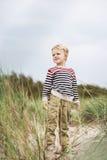 Όμορφο παιδί που στέκεται στους αμμόλοφους και που προσέχει κάτι Στοκ φωτογραφίες με δικαίωμα ελεύθερης χρήσης