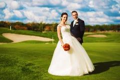 Όμορφο παντρεμένο ζευγάρι στον τομέα γκολφ Στοκ Εικόνες
