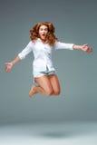 Όμορφο πηδώντας κορίτσι που απομονώνεται στο μπλε υπόβαθρο στοκ εικόνες