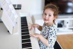 Όμορφο πιάνο παιχνιδιού κοριτσιών παιδάκι στο καθιστικό ή το σχολείο μουσικής Στοκ φωτογραφία με δικαίωμα ελεύθερης χρήσης