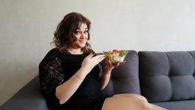 Όμορφο πλήρες κορίτσι με τη σαλάτα στον καναπέ ευτυχή, διατροφή απόθεμα βίντεο