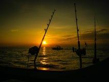 Όμορφο πορτοκαλί ωκεάνιο ηλιοβασίλεμα με τους πόλους αλιείας και το αλιευτικό σκάφος Στοκ Φωτογραφία