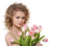 Όμορφο πορτρέτο γυναικών με τις τουλίπες λουλουδιών και τη σγουρή καταπληκτική τρίχα στοκ εικόνες