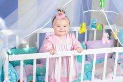 Όμορφο πορτρέτο ενός μικρού κοριτσιού σε ένα ρόδινο φόρεμα σε έναν βρεφικό σταθμό στοκ φωτογραφία
