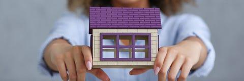 Όμορφο πορτρέτο μαύρων γυναικών Κρατά ένα μικροσκοπικό σπίτι κουκλών παιχνιδιών Στοκ Εικόνες