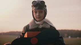 Όμορφο πορτρέτο που πυροβολείται του μικρού κοριτσιού πειραματικό κοστούμι αεροπλάνων διασκέδασης στο αναδρομικό που εξετάζει τη  φιλμ μικρού μήκους