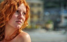 Όμορφο πορτρέτο στην κινηματογράφηση σε πρώτο πλάνο μιας νέας κομψής κοκκινομάλλους σγουρής γυναίκας θαλασσίως στο ψαροχώρι στην  στοκ φωτογραφία με δικαίωμα ελεύθερης χρήσης