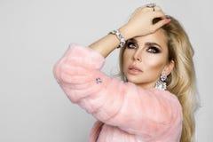 Όμορφο, προκλητικό ξανθό πρότυπο, που ντύνεται μόνο στην κομψή ρόδινη γούνα και lingerie Στοκ Εικόνες