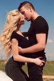 Όμορφο προκλητικό ζεύγος στα περιστασιακά ενδύματα που θέτουν εκτός από το αυτοκίνητο Στοκ φωτογραφία με δικαίωμα ελεύθερης χρήσης