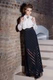 Όμορφο προκλητικό κομψό κορίτσι στο φόρεμα βραδιού σε μια άσπρη μπλούζα και πολύ μαύρη φούστα, φόρεμα στη Παραμονή Πρωτοχρονιάς,  στοκ φωτογραφία