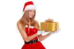 Όμορφο προκλητικό κορίτσι που φορά τα ενδύματα Άγιου Βασίλη με το δώρο Χριστουγέννων Στοκ Εικόνα