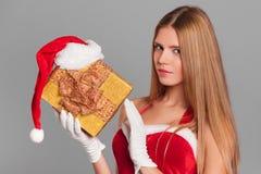 Όμορφο προκλητικό κορίτσι που φορά τα ενδύματα Άγιου Βασίλη με το δώρο Χριστουγέννων Στοκ Εικόνες