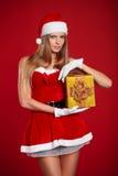 Όμορφο προκλητικό κορίτσι που φορά τα ενδύματα Άγιου Βασίλη με το δώρο Χριστουγέννων Στοκ Φωτογραφία