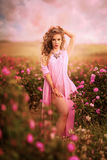 Όμορφο προκλητικό κορίτσι σε ένα ρόδινο φόρεμα που στέκεται στα τριαντάφυλλα κήπων Στοκ Φωτογραφία
