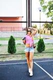 Όμορφο προκλητικό κορίτσι στα σορτς και τα γυαλιά ηλίου που θέτουν με το παλαιό έκκεντρο Στοκ Φωτογραφία