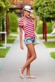 Όμορφο προκλητικό κορίτσι στα σορτς και τη ριγωτή μπλούζα, στο καπέλο, υπαίθρια Μαυρισμένο κορίτσι το καλοκαίρι Στοκ Φωτογραφία