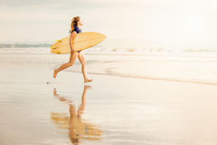 Όμορφο προκλητικό κορίτσι surfer στην παραλία στο ηλιοβασίλεμα στοκ εικόνες