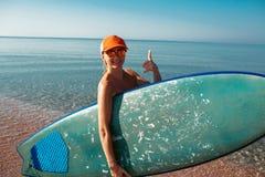 Όμορφο προκλητικό κορίτσι surfer στην παραλία Στοκ Εικόνες