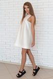 Όμορφο προκλητικό τολμηρό μοντέρνο κορίτσι στο άσπρο φόρεμα στα καθιερώνοντα τη μόδα μαύρα παπούτσια που θέτουν κοντά σε έναν άσπ Στοκ φωτογραφία με δικαίωμα ελεύθερης χρήσης